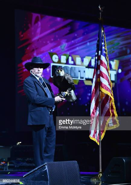 Handler holds a bald eagle named Challenger as the American national anthem is performed during Celebrity Fight Night XXIV on March 10 2018 in...