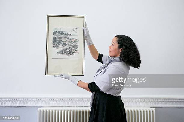 A handler holds 'Waiting for the Ferry in Sichuan' by Huang Binhong at the ICA on December 13 2013 in London England The Ashmolean Museum unveiled...