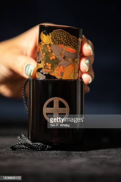 """Handler inspects a Fine and Rare Black Lacquer Three Case Saya Inro with an estimate of £7,000 to £8,000 during the """"Last Treasures From The Wrangham..."""
