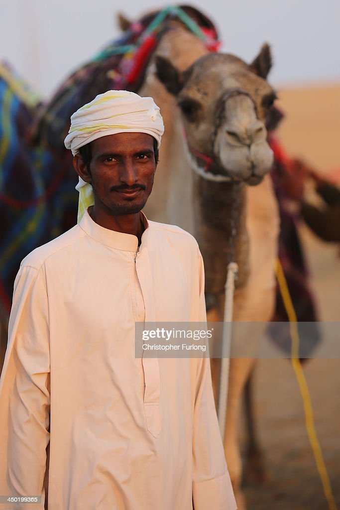 A handler waits to race at Dubai Camel Racing Club during the Al Marmoum camel racing season on November 17, 2013 in Dubai, United Arab Emirates. Camel racing is one of the oldest sports in the Middle East. Historically children from India were used as jockeys on the camels until it was outlawed in 2002. Today robot jockeys are used and include shock absorbers and GPS tracking systems. The camel's owners control the robot's whips from their speeding four wheel drives at the side of the track. Throroughbred racing camels can be as valuable as one million US dollars.