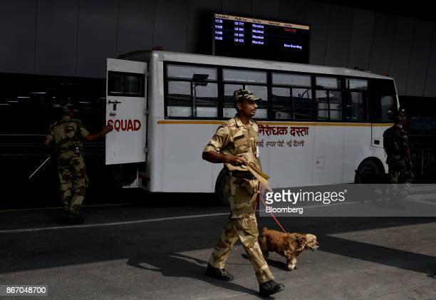 A handler walks with a dog outside the newly inaugurated Terminal 2 building at the Indira Gandhi International Airport in Delhi India on Friday Oct...