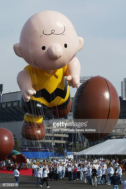 Handlers keep a tight rein on Charlie Brown and his football as balloons are tested out in the parking lot at Giants Stadium in preparation for...
