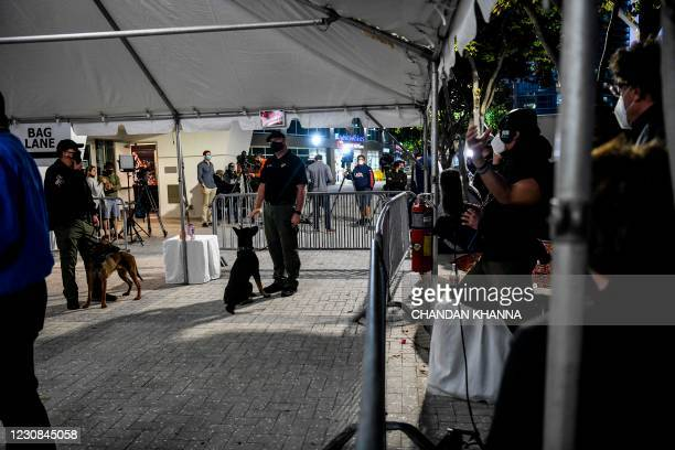Handlers stand with specially trained dogs that detect coronavirus in people at the American Airlines Arena prior to the NBA basketball match between...