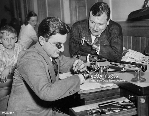 Handless Navy vet Ralph Padavano and actor Harold Russell go over watch repairing gadgets invented by Ralph at Bellevue Hospital
