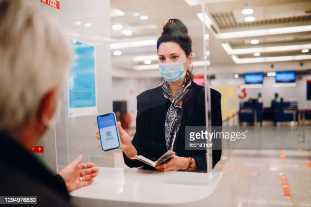 handling agent at the airport checking covid passport - passport stock pictures, royalty-free photos & images
