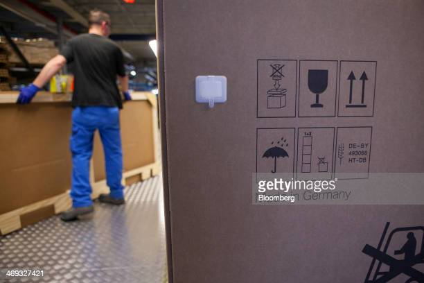 Handling instructions and Made in Germany sit on a cardboard box as an employee packages a motorbike for shipping at the Bayerische Motoren Werke AG...