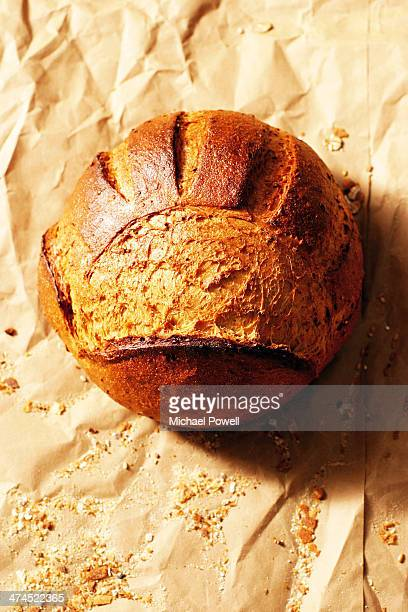 Handmade artisan French boule bread loaf on brown