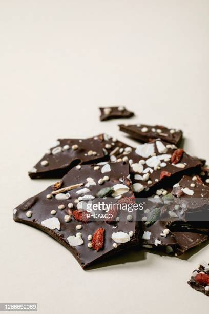 Handmade chopped dark chocolate with different superfood additives seeds and goji berries over beige background.