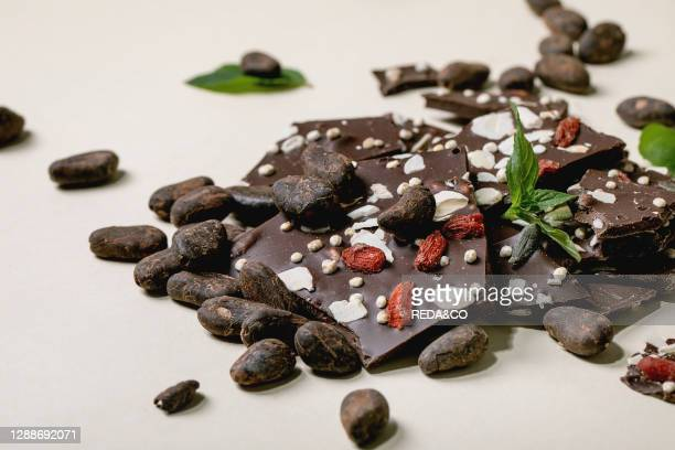 Handmade chopped dark chocolate with different superfood additives seeds and goji berries, with cocoa beans and fresh mint over beige background.