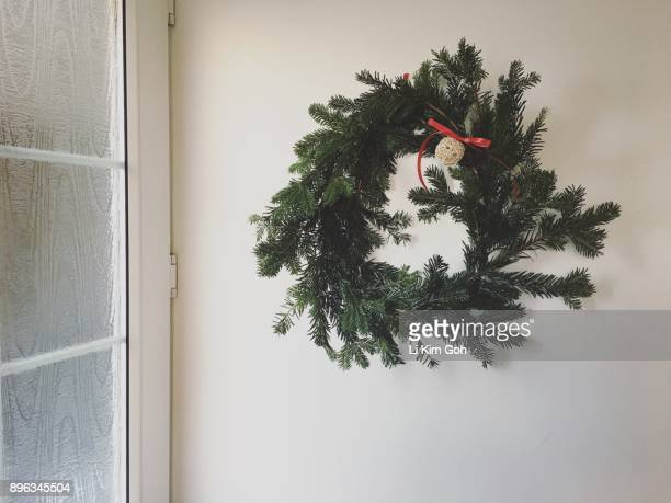 A handmade Christmas wreath handing on the wall by the door in an English home, Oxfordshire, England