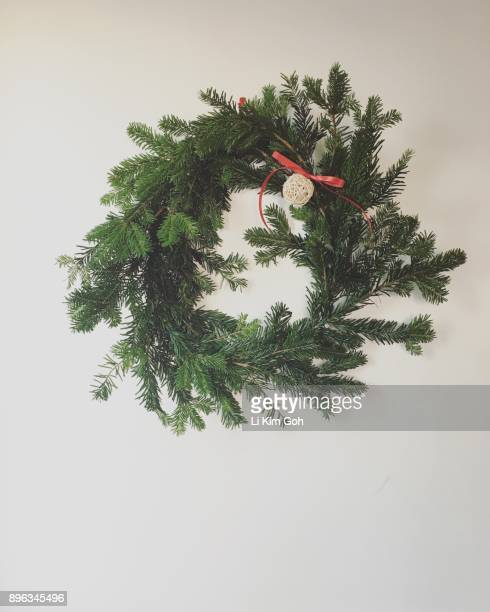 A handmade Christmas wreath made from leftover branches from a Christmas tree, hanging on white wall