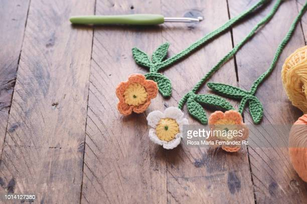 Handmade crocheted daisies, crochet hook and ball of wool in rustic wooden background. Selective focus and copy space