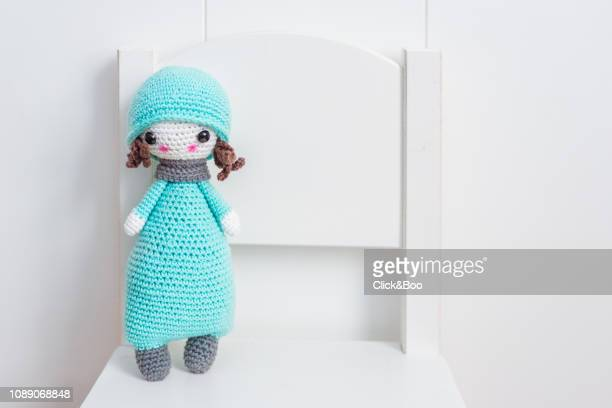 handmade crocheted doll in blue with scarf and hat on a white chair. - doll stock pictures, royalty-free photos & images