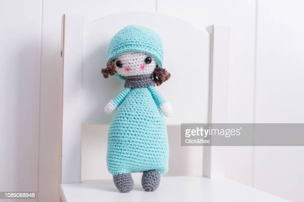 Handmade crocheted doll in blue with scarf and hat on a white chair.