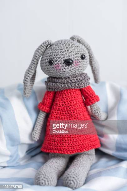 handmade crocheted doll in red with scarf on a bed - click&boo fotografías e imágenes de stock