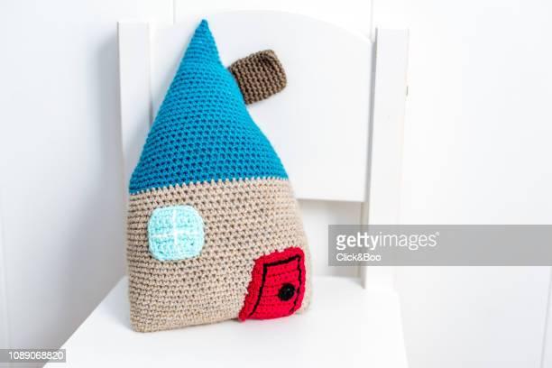 Handmade crocheted doll's house on a white chair