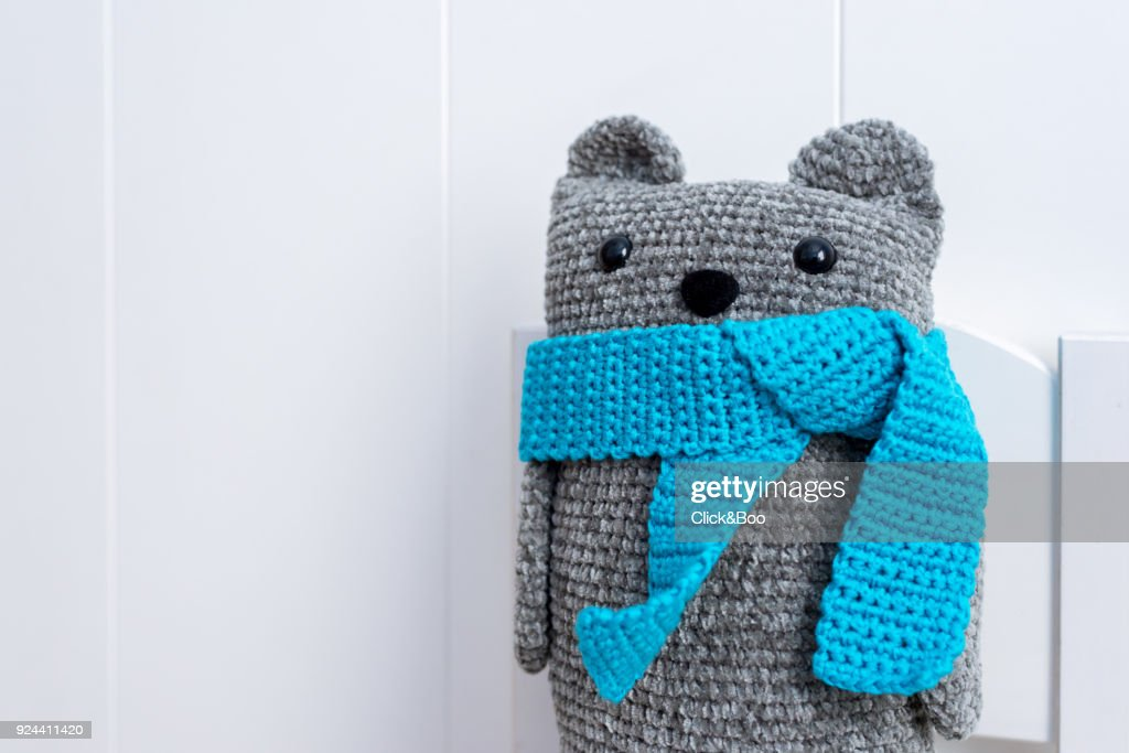 Handmade crocheted teddy bear with a blue scarf : Stock Photo