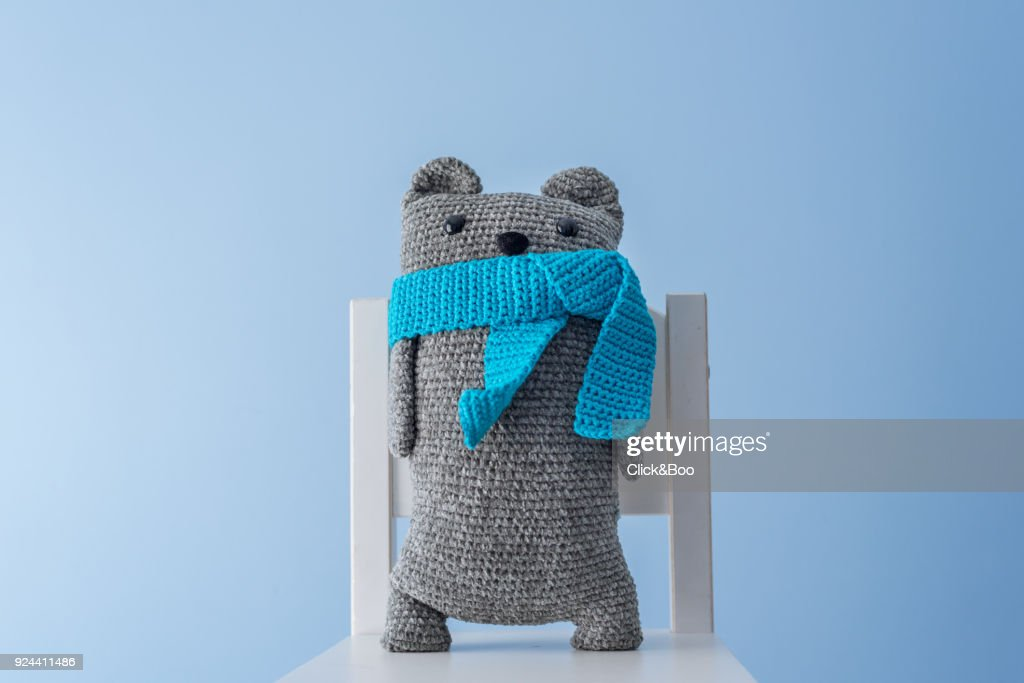 Handmade crocheted teddy bear with a blue scarf : Foto de stock