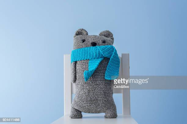 handmade crocheted teddy bear with a blue scarf - bufanda fotografías e imágenes de stock