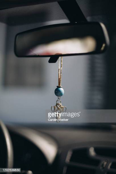 handmade cross hanging from a rear view mirror in a car as a sign of protection and faith. - car decoration stock pictures, royalty-free photos & images