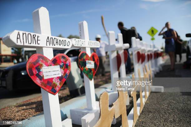 Handmade crosses memorializing the victims of a mass shooting which left at least 22 people dead are lined up before being carried to a nearby...