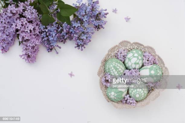 Handmade Easter eggs in a basket and Lilac flowers