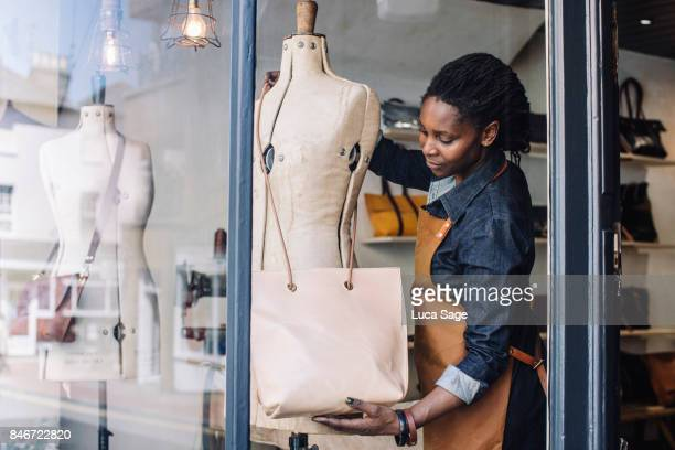 a handmade handbag store owner dresses her shop window - shop window stock pictures, royalty-free photos & images