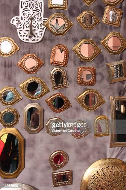 handmade mirrors with hamsa or hand of fatima at a market in souk market fez, morocco, africa - hamsa symbol stock photos and pictures