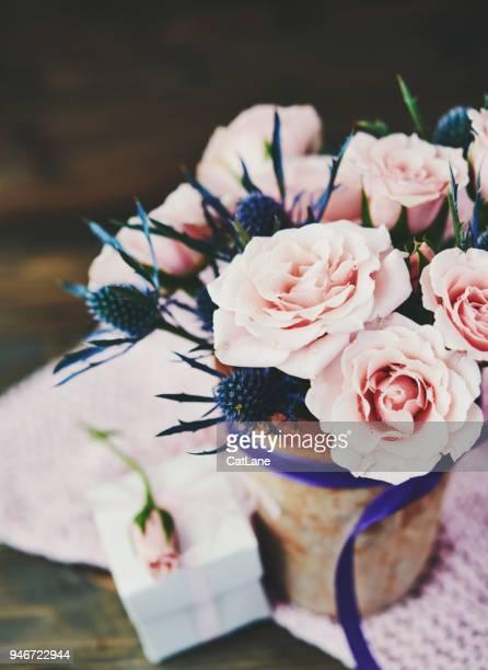 handgemachte muttertag blumenstrauß mit rosa rosen und geschenk in rustikalem ambiente - muttertag blumen stock-fotos und bilder