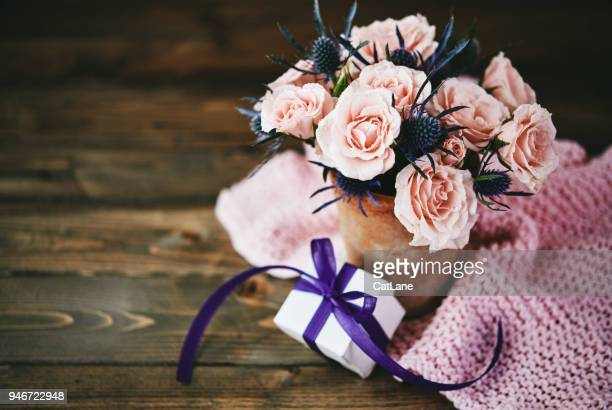 handmade mother's day bouquet with pink roses and gift in rustic setting - mother's day stock pictures, royalty-free photos & images