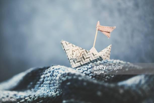 Barco de origami hecho a mano en olas hechas a mano