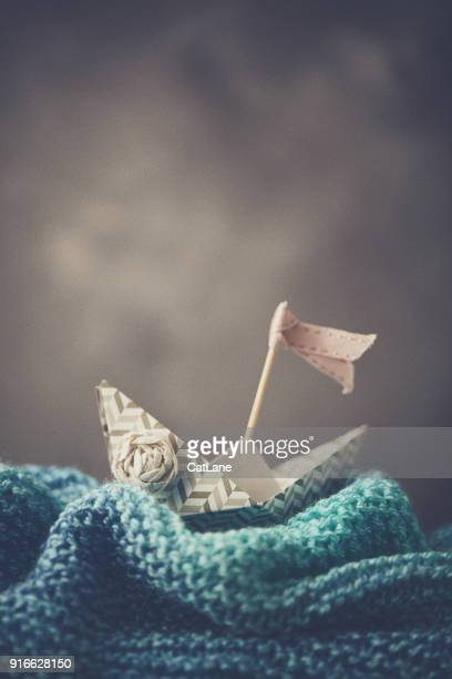 Handmade origami boat on handmade waves with stormy sky