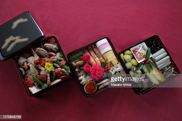 handmade osechi   - traditional japanese new year's dishes  packed in three-tiered traditional japanese lacquer coating jubako boxes ( aizu lacquer coating ) - osechi ryori stock pictures, royalty-free photos & images