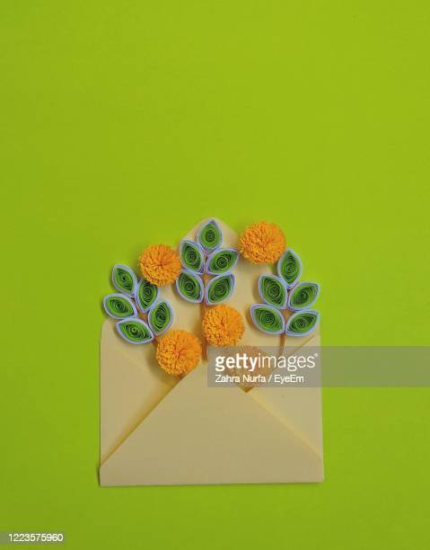 handmade paper quilling flowers in yellow envelope with green background - central kalimantan stock pictures, royalty-free photos & images