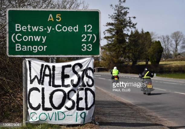 """Handmade sign attatched to a road sign near the village of Cerrigydrudion in north Wales on March 23 declares that due to the Covid 19 virus, """"Wales..."""