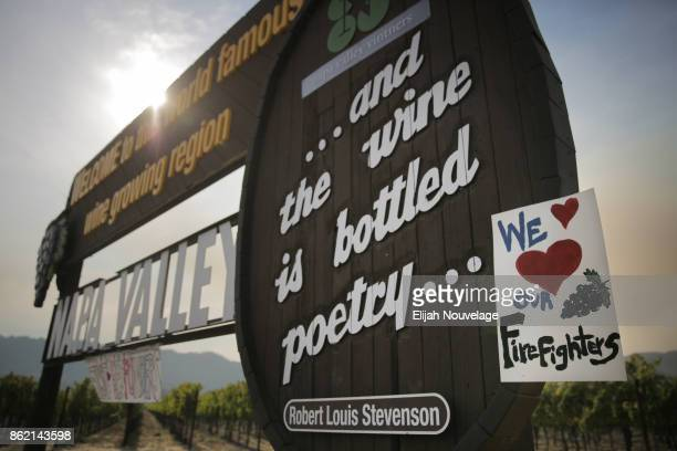 Handmade sign is seen attached to the Napa Valley welcome sign on October 16, 2017 in Oakville, California. At least 40 people are confirmed dead,...