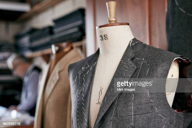 handmade suit with stitching visible hanging on mannequin - tailor stock photos and pictures