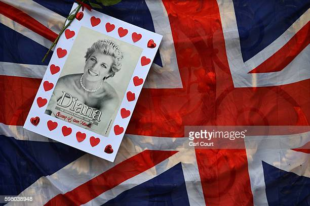 A handmade tribute to Princess Diana is hung next to a Union flag on a gate to Kensington Palace on August 31 2016 in London England Flowers flags...
