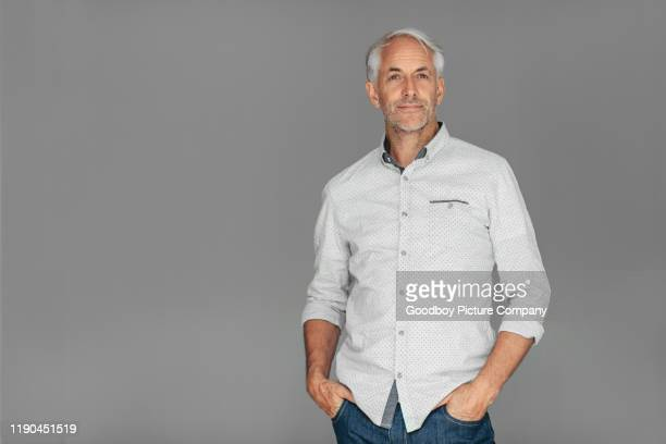 handomse mature man standing against a gray background - gray shirt stock pictures, royalty-free photos & images