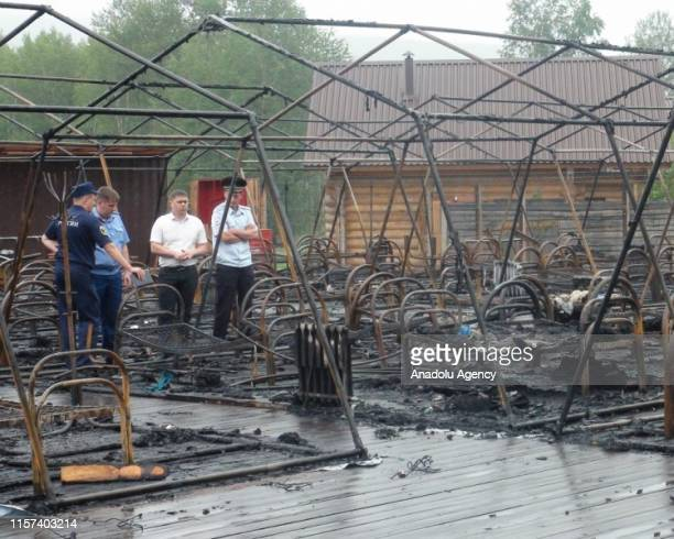 A handout photo made available by the Khabarovsk regional Emergencies ministry shows officials inspect burnt tents in a children camp after a fire...