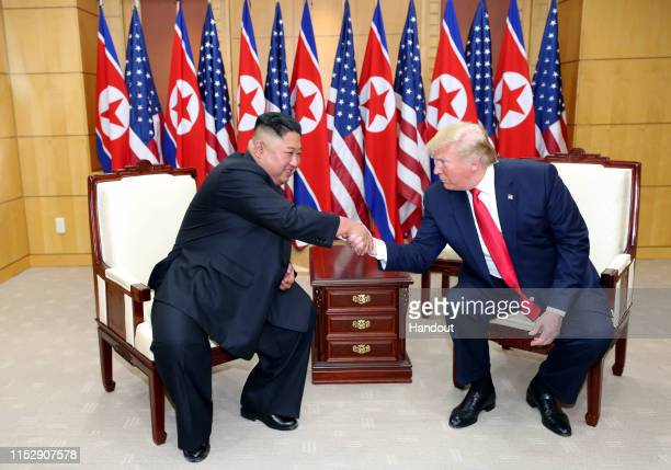 A handout photo provided by DongA Ilbo of North Korean leader Kim Jong Un and US President Donald Trump attend a meeting on the south side of the...