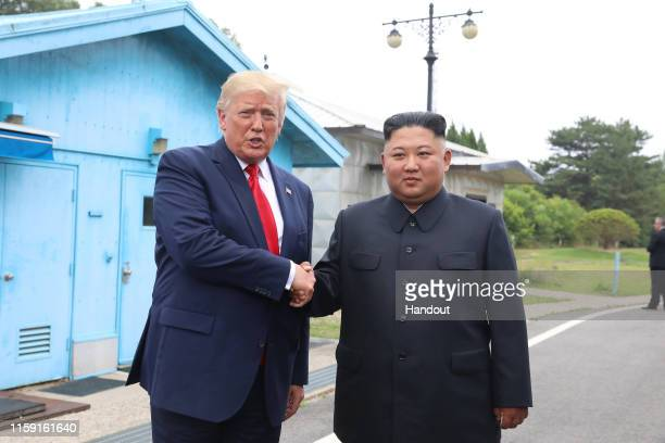 A handout photo provided by DongA Ilbo of North Korean leader Kim Jong Un and US President Donald Trump inside the demilitarized zone separating the...