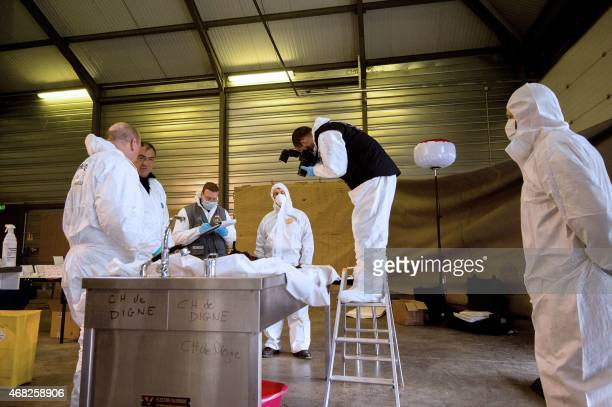 Handout photo taken on March 28, 2015 in Seyne-les-Alpes by the French Gendarmerie Nationale shows forensic experts of the French gendarmerie...