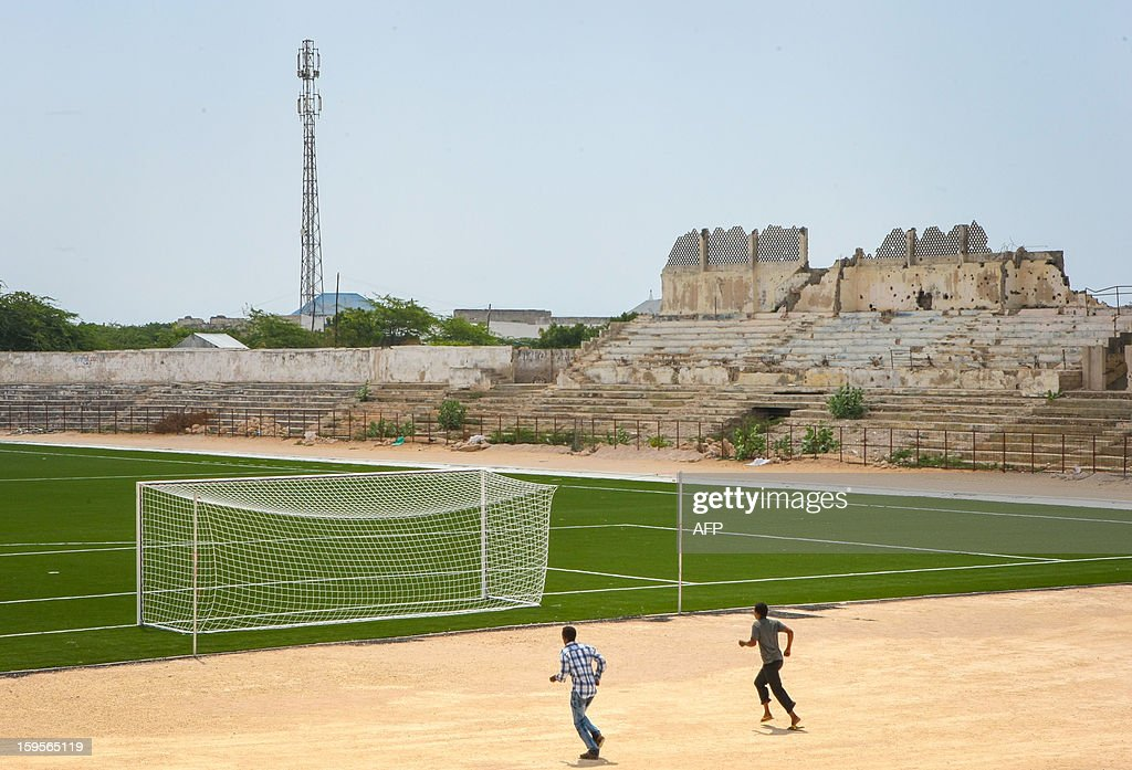 A handout photograph taken on January 12, 2013 and released on January 16 by the African Union-United Nations Information Support Team, shows two Somali men jogging near the football pitch inside Baanadir Stadium in the Abd-Aziz District of the Somali capital Mogadishu. The field that has recently been re-surfaced with a new artificial playing surface funded by FIFA, the SFF with repair work to begin on the seats, parking and facilities of the 7,500-capacity stadium. After two decades of near-constant conflict, Somalia is enjoying its longest period of peace and growing security since the Al-Qaeda-allied violent extremist group Al Shabaab was driven from Mogadishu in August 2011. Under the Shabaab's draconian rule, social pastimes and sports such as football were banned but residents of the city and elsewhere across Somalia.