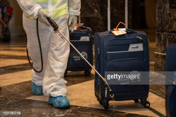Handout picture provided by the Saudi Ministry of Media on July 26 shows a worker sanitising pilgrims' luggage in a hotel lobby located near the...