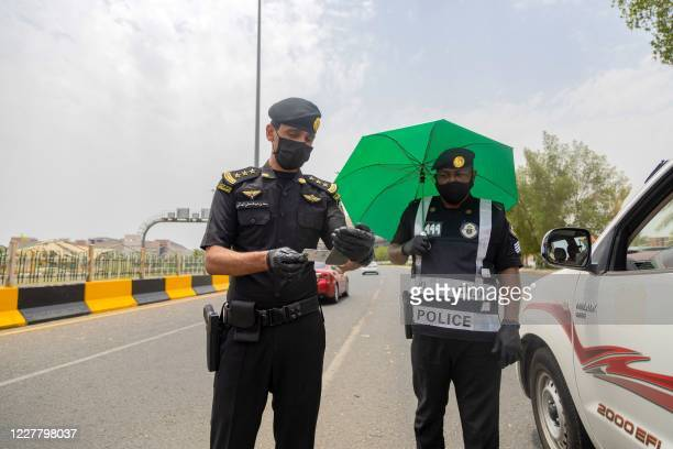 Handout picture provided by the Saudi Ministry of Media on July 26 shows a policeman checking the identity of a driver in Saudi Arabia's holy city of...