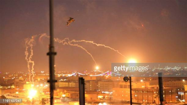 TOPSHOT A handout picture received from the US embassy in Iraq on December 31 shows a US army apache helicopter dropping flares over Baghdad's...
