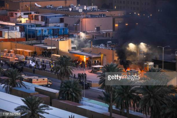 Handout picture received from the US embassy in Iraq on December 31 shows smoke billowing from a sentry box at an entrance of the embassy in the...
