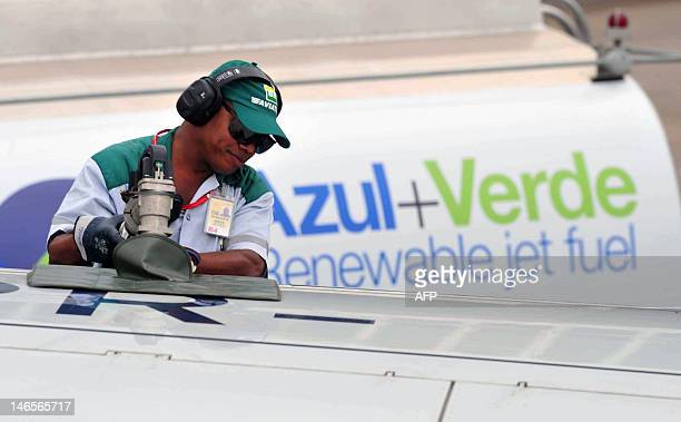 Handout picture released by Embraer of an employee fuelling up an Embraer 195 plane with renewable jet fuel produced from Brazilian sugarcane, on...