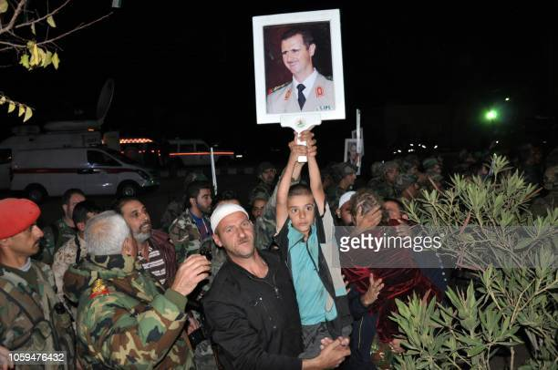 Handout picture released by the official Syrian Arab News Agency on November 9, 2018 shows a boy holding up a picture of the Syrian President Bashar...